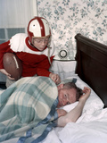 Boy in Football Uniform Waking Father Asleep in Bedroom