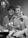 1950s Husband and Wife Carrying Armload of Christmas Packages Standing in Snow under Porch Light