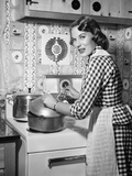1950s Housewife Wearing Checkered Dress Standing in Kitchen Stirring Pot on Stove