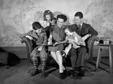 1930s-1940s Family Sitting on Couch Looking Reading Book Together