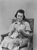 Brunette Woman Knitting Sitting in Armchair