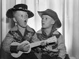 1950s 2 Juvenile Boys in Cowboy Hat and Shirts Playing Ukulele and Singing Mouth Open Wide