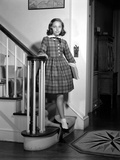 1950s Teenage Girl in Plaid Dress and White Ankle Socks on Stairway Holding Banister