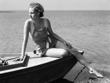 Woman Wearing One Piece Bathing Suit Sitting on Edge of Boat