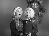 1960s Boy and Girl Singing Christmas Carol Together under Snowy Outdoor Porch Light