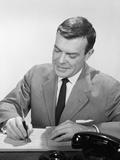 Smiling Businessman at Desk Writing Checks