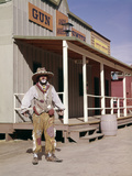 1960s Sad Clown in Cowboy Costume Standing in Street of Western Frontier Town