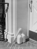 Glass Milk Bottles and Newspaper by Front Door Home Delivery