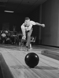 Man Releasing Ball Down Bowling Alley Lane