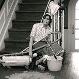 1960s-1970s Exhausted Housewife Sitting at Bottom of Stairs Surrounded by House Cleaning Equipment