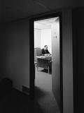 Executive Businessman at Desk Seen Working Late Through Door Ajar