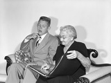 1950s Teen Boy in Suit with Candy Box Sits Next to Old Woman