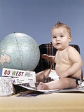 1960s Baby Boy Sitting by World Globe with Suitcase and Travel Paraphernalia