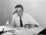 Businessman Desk Full Papers Hand to Forehead Serious Expression
