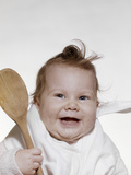 1960s-1970s Smiling Baby Wearing Bib and Holding Wooden Spoon