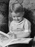 1930s-1940s Little Boy Sitting on Chair Reading Picture Book