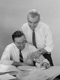 2 Businessmen in Shirt Sleeves Looking over Paperwork
