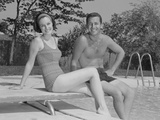Man Woman Couple Sitting on Diving Board on Side of Swimming Pool