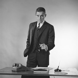 Serious Businessman Three Piece Suit Standing Behind Desk Gesturing with Glasses