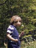 Boy Wearing Bib Overalls Blowing on Dandelion Head
