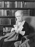 Elderly Woman Sitting before Bookcase Serious Expression Knitting