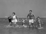 1960s Family Holding Hands Running Together in Water at Seashore