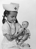1960s Girl in Nurse Uniform Holding Stethoscope to Baby Doll Chest Indoor