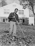 Smiling Man Raking Autumn Leaves in Front Yard of House