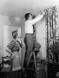 1950s Skeptical Wife in Apron Fingers Pressing Chin Watching Husband on Ladder Hanging New Drapes