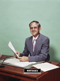 Smiling Man at Desk Holding Papers with Mortgage Officer Sign