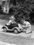 1940s-1930s Boy on Sidewalk Fixing Headlight of Toy Car Driven by Little Girl Playing Outdoor
