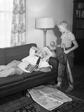 1950s Father on a Sofa with Newspaper While Son Is Standing over Him with Baseball Equipment