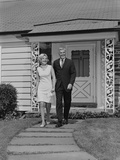 Mature Couple Walking on Sidewalk Front of House