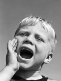 1950s Blond Boy with Eyes Closed and Hand Cupping a Wide Open Mouth Shouting