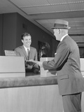 Businessman Making a Deposit into Savings Account with Bank Teller