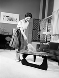 1950s-1960s Woman Wearing a White Blouse and Plaid Skirt Dusting with a Feather Duster