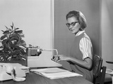 Secretary Typist Wearing Stylish Eyeglasses Using Manual Typewriter at Desk