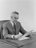 Businessman Executive Middle Aged Sitting at Desk Reading Papers