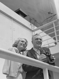 Smiling Mature Couple at Shipboard Rail with Binoculars