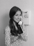 Smiling Teenage Girl Talking on Rotary Wall Telephone