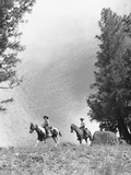 1950s-1960s Two Men on Horseback Riding across Field Wearing Cowboy Hats