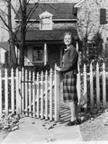 1940s Smiling Pretty Young Teenage Girl Standing by White Picket Fence in Front of Stone House