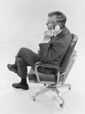 Profile Executive Businessman Sitting in Office Chair Talking on Telephone