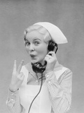 Smiling Blond Nurse with Surprised Expression Talking on Telephone Holding Up Two Fingers