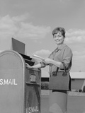 Smiling Woman Dropping Letters in Postal Mail Box