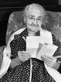 1960s Elderly Woman in Polka-Dotted Dress and Shawl Reading Letter