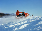 Man Wearing Red Jacket and Hat Driving Snowmobile