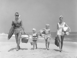 1950s Family of Four Walking Towards Camera with Beach Balls Umbrella Picnic Basket and Sand Bucket