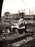 1930s Hobo Sitting by Railroad Track Reading Newspaper During Great Depression