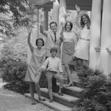 Family Group of People Standing on Steps of House Waving